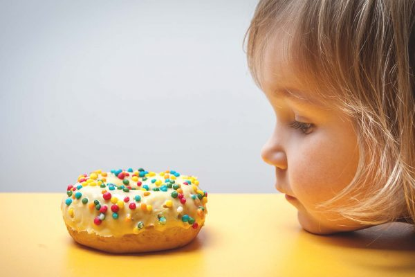 child not eating doughnut to tackle obesity and tooth decay
